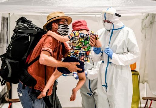 Un padre y su hijo a punto de someterse a la prueba de diagnóstico en la estación Hauptbahnhof de Berlín.