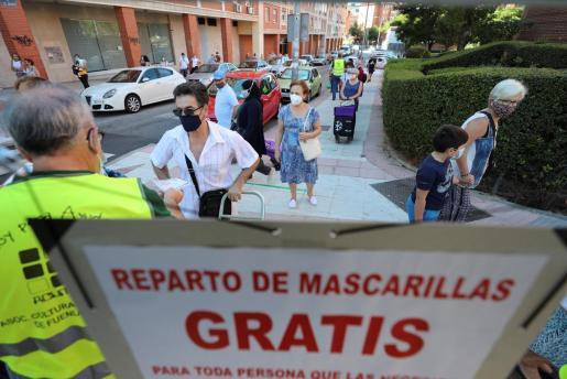 Un voluntario de la asociación de mayores Acumafu reparte mascarillas y toma la temperatura a las personas interesadas en Madrid.