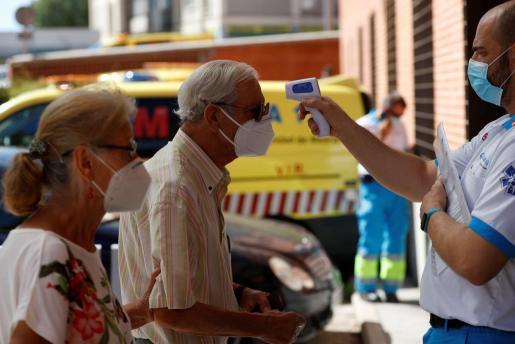 Un sanitario toma la temperatura a un hombre antes de acceder este miércoles a un centro de salud de Madrid.