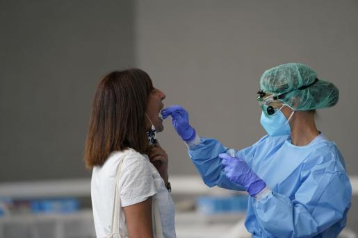 Una enfermera, tomando una muestra para realizar una PCR.