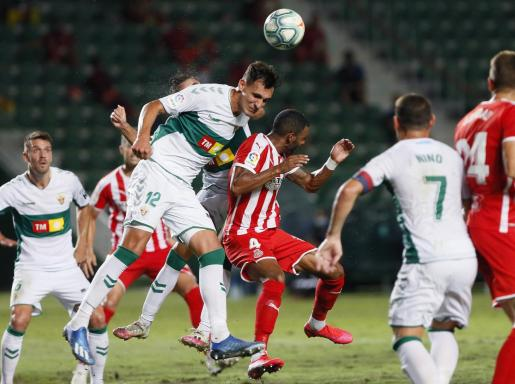 El defensa del Elche Dani Calvo (i) salta por el balón con Jonás Ramalho, del Girona, durante el primer partido de la final por el ascenso a Primera División.