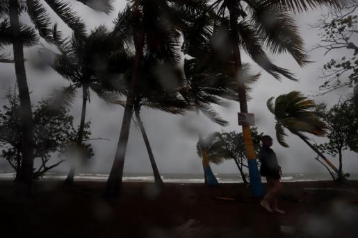 Una persona camina entre la lluvia y los fuertes vientos debido al paso de la tormenta Laura.