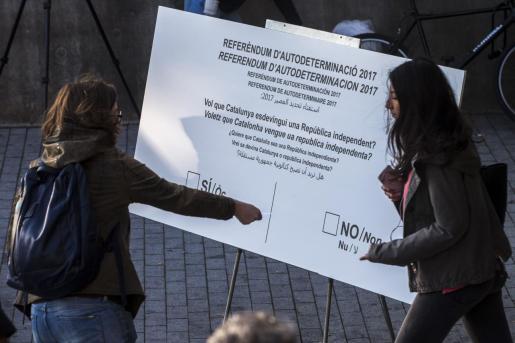 Miembros de la CUP, repartiendo papeletas en el centro de Barcelona en el marco de una campaña sobre el referéndum de independencia en Cataluña.