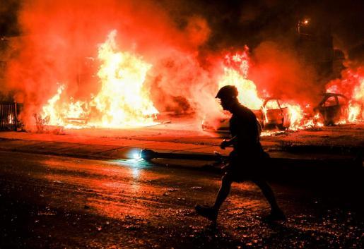 La silueta de un hombre ante varios coches incendiados durante la segunda noche de disturbios tras el tiroteo de Jacob Blake por parte de agentes de policía, en Kenosha, Wisconsin.