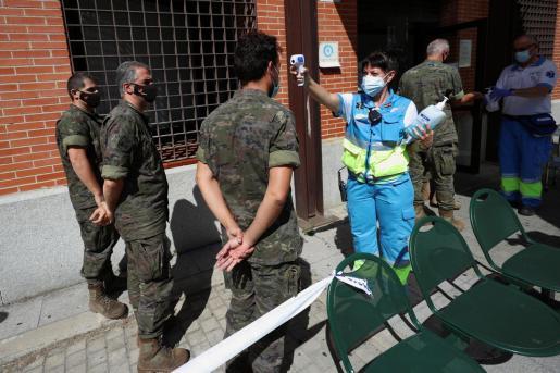 Una trabajadora sanitaria toma la temperatura a varios militares antes de acceder al centro sanitario para realizarse una prueba PCR en Madrid.