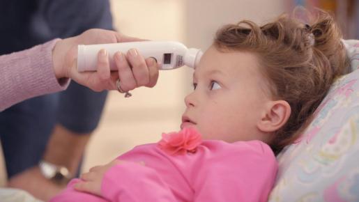 Imagen de una niña a la que le toman la temperatura.