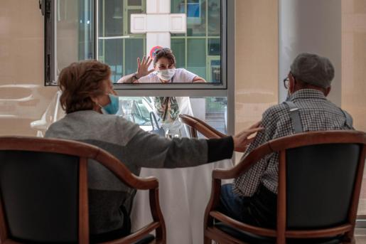 Una persona conversa con sus padres a través de una ventana habilitada en la residencia de mayores.