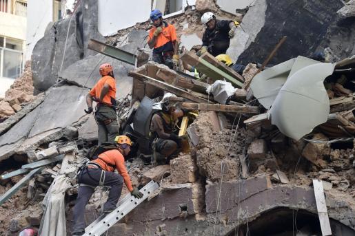 Miembros de un equipo de rescate entre escombros en Beirut.