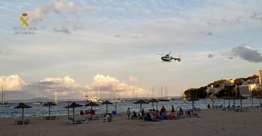 El helicóptero de la Guardia Civil sobrevuela una playa mallorquina y anuncia la nueva normativa.