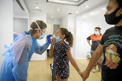Isabela Jiménez, de 9 años, es sometida a la prueba mientras coge a su madre de la mano.