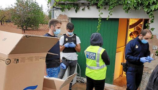 Los agentes de la Policía Nacional y de la Local, durante la operación del lunes, junto a cajas y material localizado en la casa.