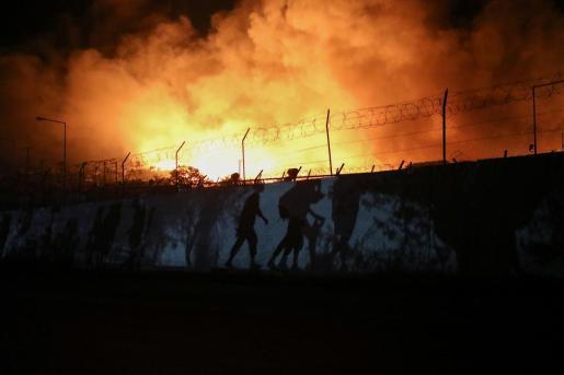 Refugiados y migrantes cargan con sus pertenencians huyendo del campo incendiado con un destino incierto.