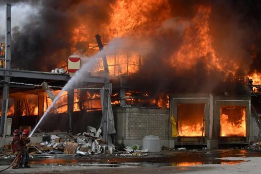 Bomberos de Beirut sofocando las impresionantes llamas del incendio de este jueves en el puerto libanés.