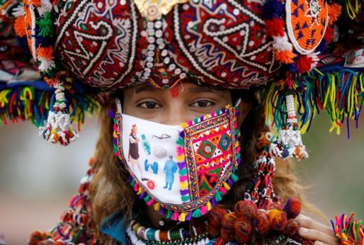 Una participante en un baile tradicional, con una mascarilla.