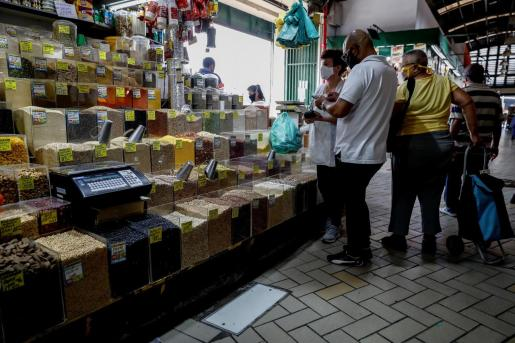 Consumidores compran alimentos básicos en un mercado popular en la ciudad de Sao Paulo (Brasil).