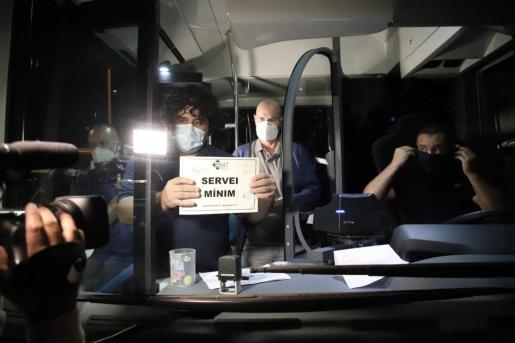 Un conductor coloca el cartel de servicio mínimo a un autobús de la EMT, cuyos trabajadores inician huelga este lunes.