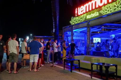 Un empleado toma la temperatura a una joven que hace cola para entrar en un pub en el puerto deportivo de Marbella.