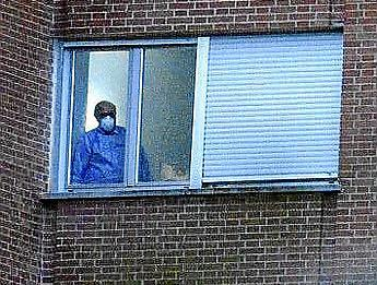 Una persona con una mascarilla se asoma esta tarde por una de las ventanas de un hospital.