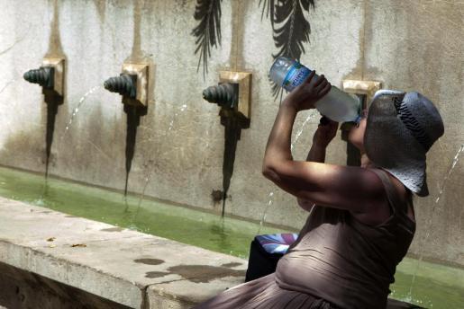 Una turista se refresca a la sombra en Palma.