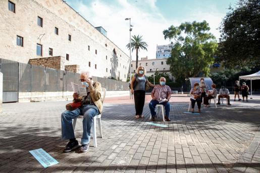 Varias personas esperan para acceder a la zona de realización de PCR durante el primer día de cribados masivos de Covid-19 en El Raval de Barcelona.
