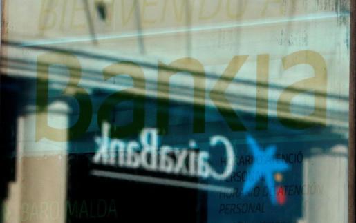 El logotipo de Caixabank reflejado en la cristalera de una sucursal de Bankia.