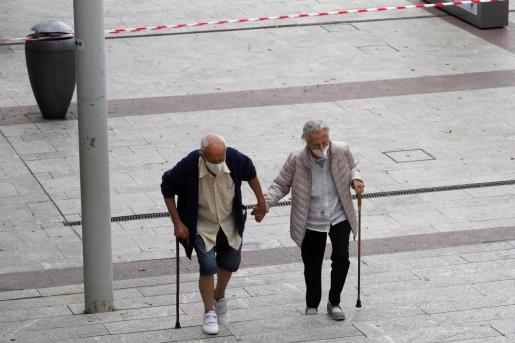 Un hombre y una mujer caminan este sábado por una calle de Alcobendas. A partir del lunes, unos 850.000 habitantes de la Comunidad de Madrid quedarán recluidos en sus barrios salvo para ir a trabajar o hacer otras actividades esenciales.