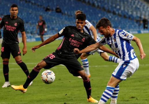 El centrocampista de la Real Sociedad, David Silva (d), golpea el balón ante el jugador del Real Madrid, Marvin Olawale, durante el encuentro correspondiente a la segunda jornada de primera división disputado esta noche en el estadio Reale Arena de San Sebastián.