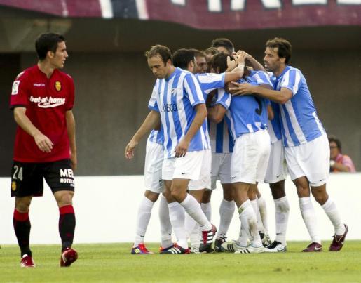 Los jugadores del Málaga CF celebran su gol ante la mirada del delantero del RCD Mallorca, Alejandro Alfaro (i), durante el partido correspondiente a la cuarta jornada de la Liga en Primera División del año pasado.