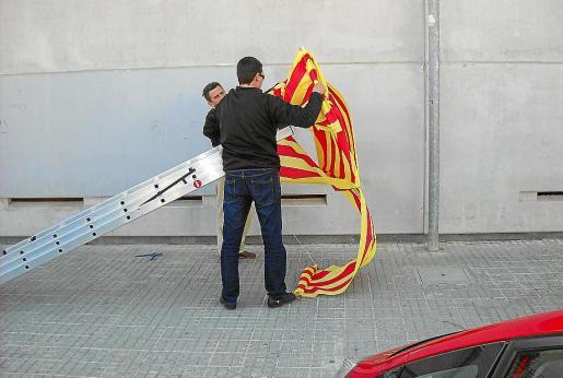 Operarios de Educació retirando un lazo por el catalán el pasado curso escolar.