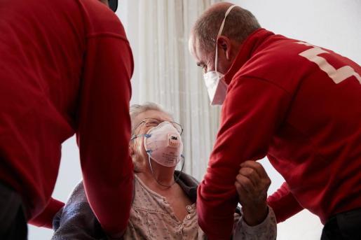 Varios sanitarios atiende a una persona mayor.