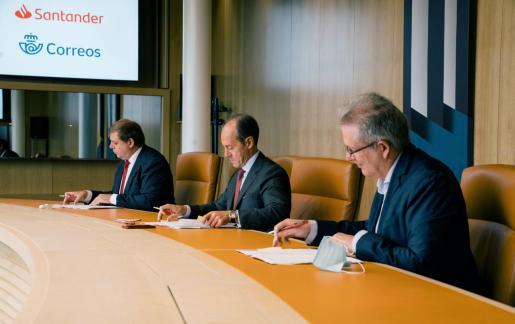 El presidente de Correos, Rami Aboukhair; el consejero delegado de Santander España, Rami Aboukhair; y el secretario general de Correos, Julio González; asisten a la firma del acuerdo.