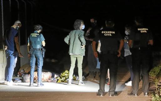El cadáver del presunto ladrón aparece en la calzada junto al forense e investigadores.