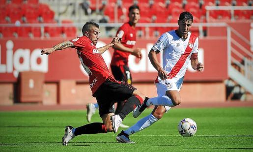 Dani Rodríguez intenta despejar el balón ante Comesaña, futbolista del Rayo, durante el primer partido del campeonato en Son Moix.