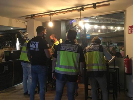 Operativos. Agentes de la Policía Nacional y Policía Local revisando la documentación en uno de los locales inspeccionados.