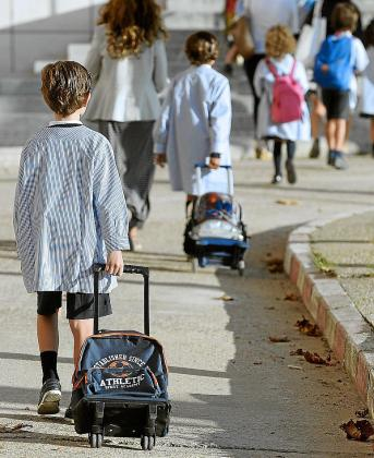 Un grupo de niños acuden a su centro escolar.