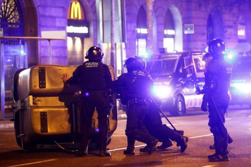 Mossos d'Esquadra retiran contenedores volcados por los manifestantes que ha participado esta noche en las calles de Barcelona, después de que el Tribunal Supremo confirmase la condena de año y medio de inhabilitación al presidente de la Generalitat, Quim Torra.