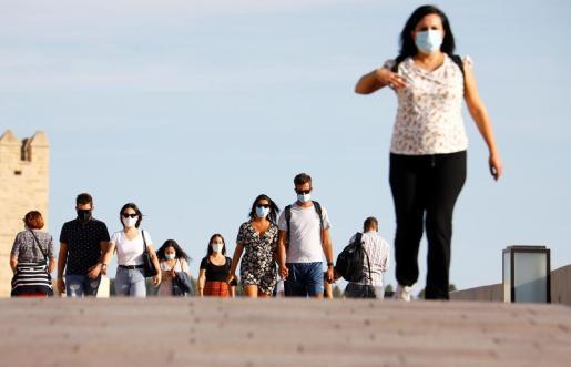 Varias personas caminan por las calles del casco histórico de Córdoba protegidas con mascarillas.