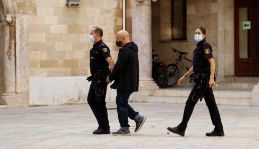 El acusado, escoltado por la Policía Nacional, antes de entrar al juicio este martes.