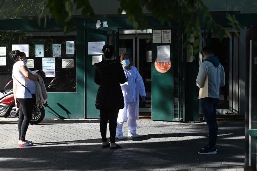 Varias personas conversan con una sanitaria del centro de salud del barrio de García Noblejas, en el distrito madrileño de Ciudad Lineal.