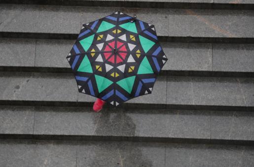 Una mujer se protege de la lluvia con un paraguas.