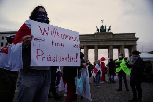 Concentración de ciudadanos bielorusos frente a la Puerta de Brandemburgo ante la visita de la líder opositora Sviatlana Tsikhanouskaya. Todos los participantes, ataviados con mascarillas.