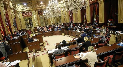 Sobre estas líneas, una imagen de la sesión plenaria del pasado martes 29 de septiembre. Hay escaños que quedan sin ocupar y los diputados y las diputadas entran y salen según el tema de debate. No hay plazo para retomar la normalidad.