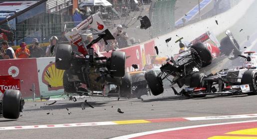 El piloto español de la escudería Ferrari Fernando Alonso (i) y el británico de McLaren Mercedes Lewis Hamilton (2-d) sufren un aparatoso accidente al comienzo de la carrera del Gran Premio de Bélgica.
