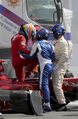 El piloto español de Fórmula Uno Fernando Alonso), de Ferrari, sale de su monoplaza tras chocar al comienzo de la carrera del Gran Premio de Bélgica.