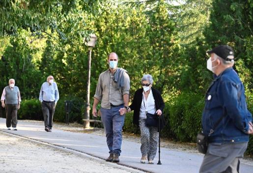 Vecinos del madrileño barrio de Moratalaz pasean este sábado por un parque de la zona.