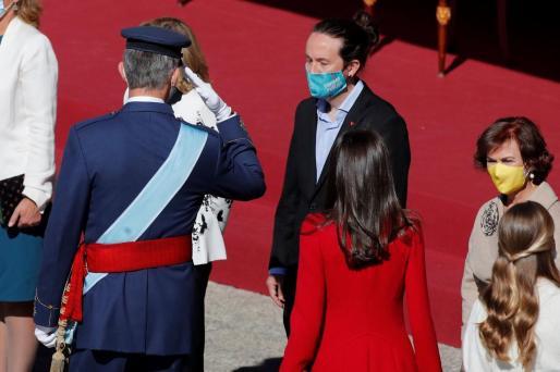 El rey Felipe saluda al vicepresidente segundo del Gobierno, Pablo Iglesias, ante la reina Letizia y la vicepresidenta, Carmen Calvo (d) durante el acto organizado con motivo del Día de la Fiesta Nacional.