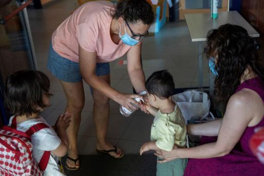 Imagen de archivo de una profesora aplicando gel hidroalcohólico en las manos de un niño.