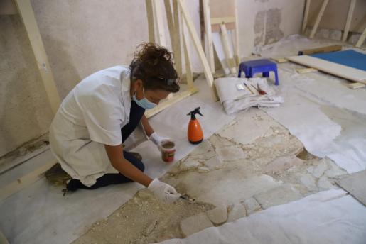 Una de las responsables de la restauración trabajando sobre el suelo de la sala medieval de Can Balaguer.