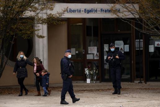 Una madre y sus hijos, después de colocar flores frente a la escuela secundaria Bois d'Aulne para presentar sus respetos ante el profesor que fue asesinado en Conflans Saint-Honorine.