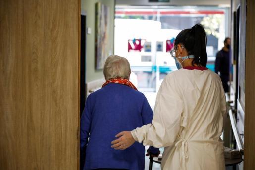 Una trabajadora de una residencia de mayores ayuda a una paciente, este lunes en las instalaciones del centro, en Madrid.